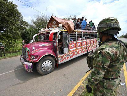 Indígenas colombianos abordo de un autobús 'chiva' pasan frente a un retén militar a las afueras de Cali, este miércoles.