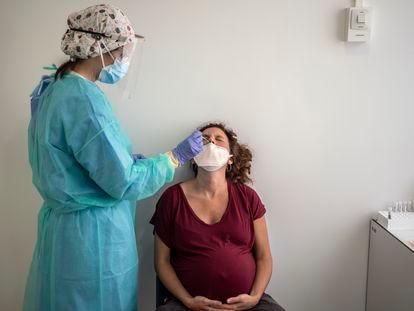 Personal médico del hospital Clínico San Carlos realiza una prueba PCR para detectar la covid-19 a una mujer embarazada.