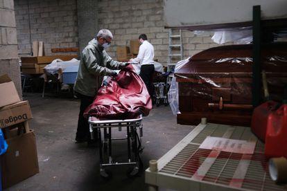 Dos trabajadores de una funeraria en Nueva York preparan el cuerpo de una fallecida por coronavirus.