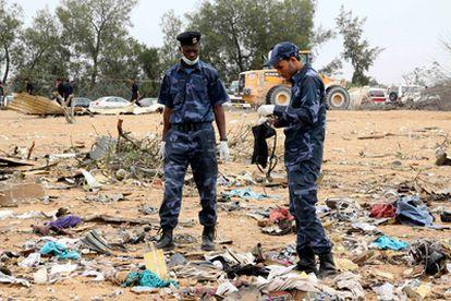 Un policía recoge una prenda de una de las víctimas del accidente aéreo.