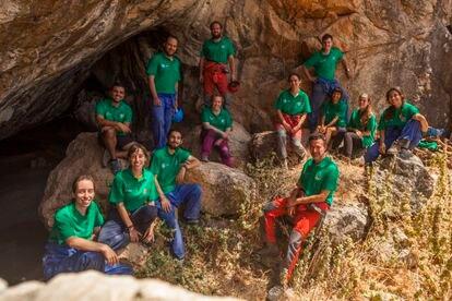 Daniel García Rivero, de pie con pantalón rojo y casco en la mano, junto al equipo de arqueólogos que trabaja en el Cueva de la Dehesilla.