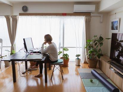 Una mujer teletrabaja desde el salón de su casa.