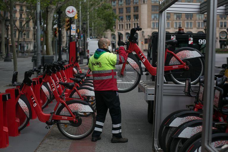 Un operario coloca bicicletas del Bicing el primer día de retomar la actividad durante la crisis del coronavirus.