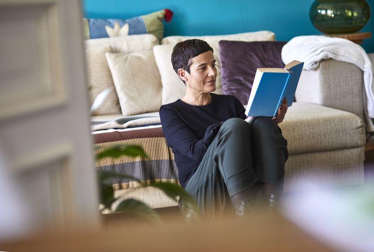 Una mujer lee un libro en su casa.