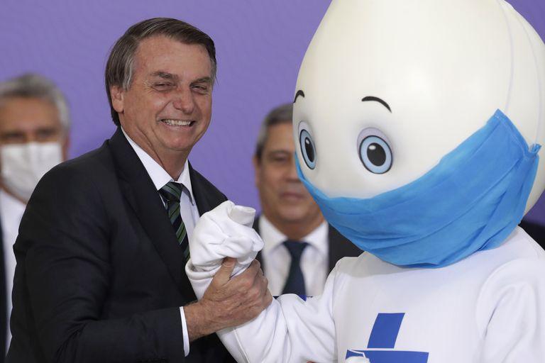 El presidente de Brasil, Jair Bolsonaro, junto a la mascota Ze Gotinha destinada a la campaña de vacunación.