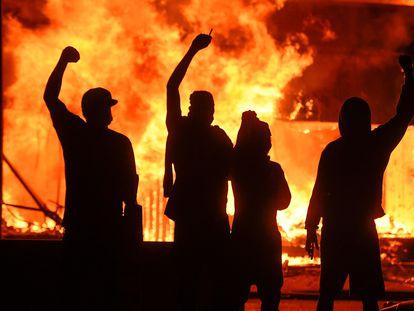 Varios manifestantes alzan el puño junto a una tienda en llamas, durante unos disturbios en Minneapolis, este sábado