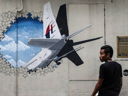Un hombre que camina junto a un mural en recuerdo del vuelo MH370 en Shah Alam, a las afueras de Kuala Lumpur (Malasia), en marzo de 2015.