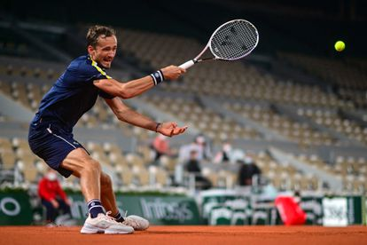 Medvedev hits the ball, with the center stands empty.