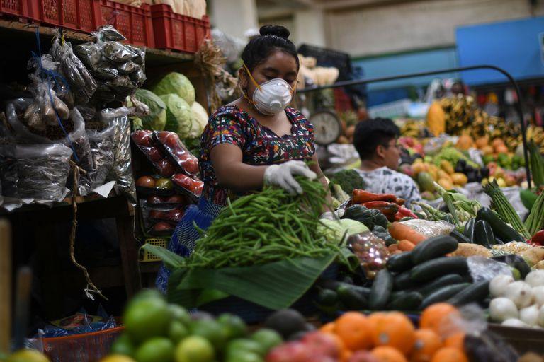Una mujer vendedora de vegetales en un mercado de ciudad de Guatemala.