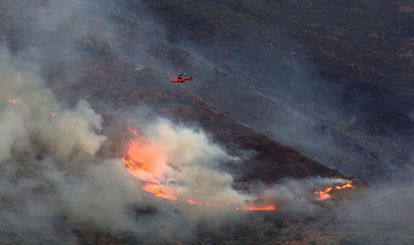 Un helicóptero intentan extinguir el incendio de Sierra Bermeja, este lunes.