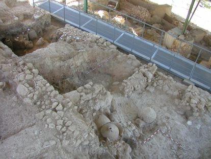 Vivienda íbera excavada con una pasarela que cruza una calle de la población. En primer plano, dos molinos rotatorios de piedra.
