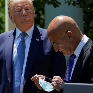 U.S. President Donald Trump looks on as former GlaxoSmithKline pharmaceutical executive Moncef Slaoui, who will serve as chief adviser on the effort to find a vaccine for the coronavirus disease (COVID-19) pandemic, removes his face mask  during a coronavirus response event in the Rose Garden at the White House in Washington, U.S., May 15, 2020. REUTERS/Kevin Lamarque - RC25PG9U9XJO