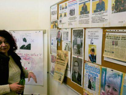Amela Hasecic muestra un tablero de la sala de terapia con fotografías y recortes de periódico.