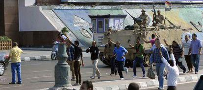 Un blindado del Ejército egipcio vigila a un grupo de manifestantes contrarios a los Hermanos Musulmanes en Alejandría.