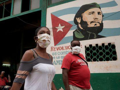 Dos peatones caminan frente a una imagen de Fidel Castro, este domingo en La Habana.