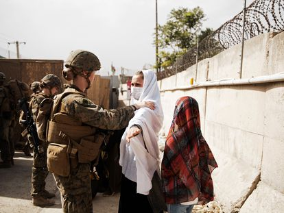 Una soldada registra a una civil el 18 de agosto de 2021 en el aeropuerto de Kabul, Afganistán.