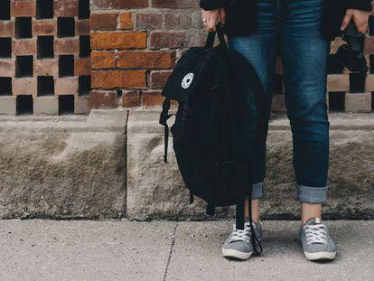 Una adolescente sujeta su mochila para ir a clase.