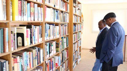 Dos usuarios contemplan los libros de la biblioteca del Centro Cultural Hargeysa.