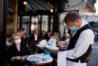 Un camarero, en la terraza de un café parisino.