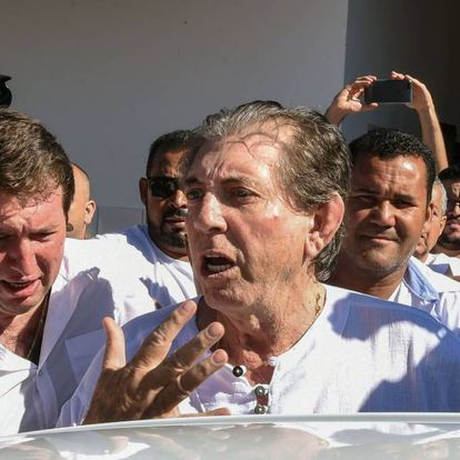 """BRAZIL-RELIGION-SEXUAL-ABUSE-JOAO DE DEUS Brazilian """"spiritual healer"""" Joao Teixeira de Faria (C), known as """"Joao de Deus"""" (John of God) is escorted by supporters, upon arrival at his """"healing center"""" Casa de Dom Inacio de Loyola, in Abadiania, 120 km southwest of Brasilia, state of Goias on December 12, 2018. An internationally famous Brazilian """"spiritual healer"""" accused by hundreds of women of sexual abuse told his followers on Wednesday """"I am not guilty"""" of the allegations stacked against him. Police are starting to investigate complaints lodged by more than 450 women in Brazil following claims by a dozen of his followers aired by Globo TV and the O Globo newspaper last week that he forced them into sex acts under pretext of curing them of ailments. EVARISTO SA / AFP"""