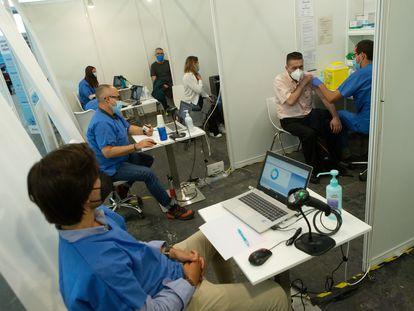 Un enfermero vacuna a un hombre en el centro de inmunización situado en la Fira de Barcelona el 11 de mayo de 2021.