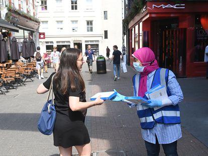Una sanitaria ofrece un test rápido a una joven que pasea por Carnaby este lunes en Londres.