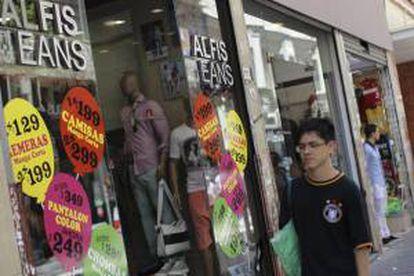 Un hombre camina frente a una tienda de ropa con avisos de promoción en el centro de Buenos Aires (Argentina). EFE/Archivo