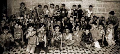 Hikmat Shaihan, de 26 años, posa, este año, junto a los niños del colegio que dirige en Alepo oriental.