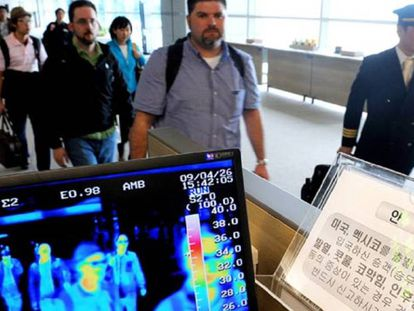 Unos viajeros pasan por un control de temperatura corporal en el aeropuerto de Seúl (Corea del Sur).