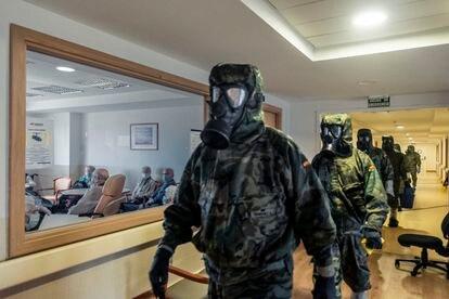 Miembros de la compañía NBQ (Nuclear, Biológico y Químico) de la brigada paracaidista de Alcalá de Henares efectúan tareas de descontaminación en una residencia de ancianos.