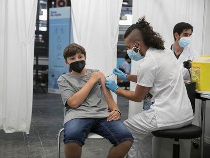Un adolescente recibe su primera dosis contra la covid-19 en el centro de vacunación de la Fira de Barcelona.