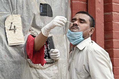 A nurse conducts a coronavirus test in India.