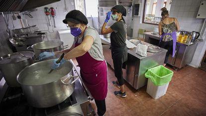 Las cocineras del colegio público Gómez Moreno de Granada preparan el menú en la cocina del centro.