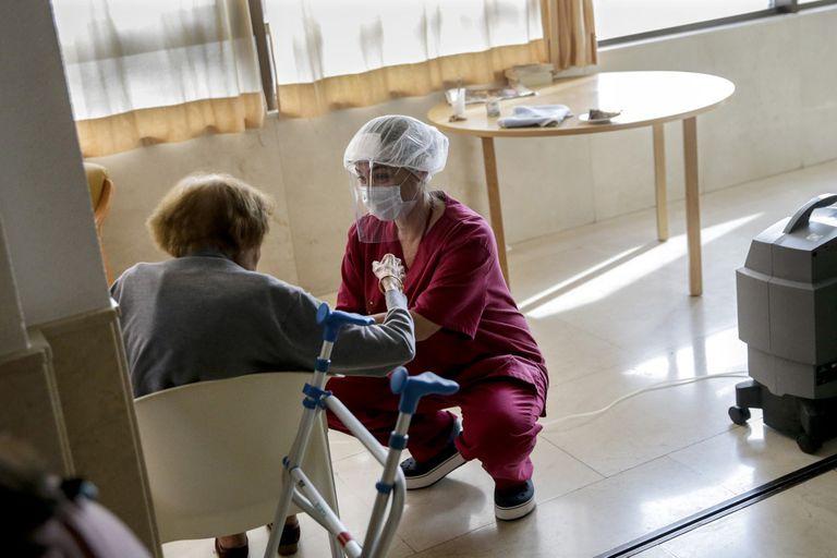 Una trabajadora protegida con un equipo contra los virus atiende a una mujer mayor en la residencia Monte Carmelo, en Madrid.
