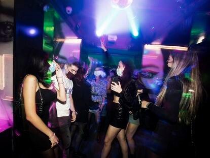 Un grupo de jóvenes baila en un local de ocio nocturno la misma noche en que entra en vigor la reapertura en interiores a medianoche, el 8 de octubre de 2021, en Madrid.