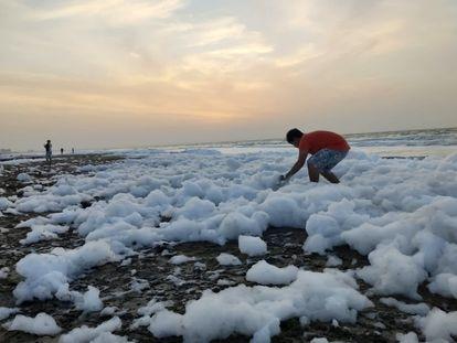 Un joven juega con la espuma a la orilla de una playa en Coatzacoalcos, Veracruz.
