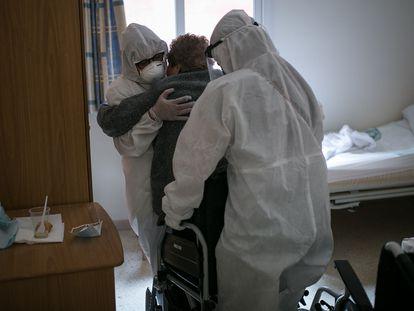 Una trabajadora de una residencia de Cataluña y una voluntaria ayudan a una mujer a sentarse en una silla de ruedas.