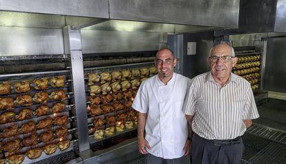 Pere Pi y su hijo Narcís, junto a algunos de los pollos que asan a diario junto a la carretera de Pals.