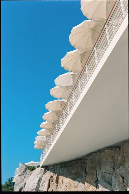 El muro de rocas y la enorme terraza del hôtel du Cap Eden Roc cubierta de sombrillas blancas.