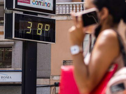 Una mujer pasa en Mallorca junto a un termómetro que muestra la temperatura en grados Celsius, el pasado agosto.