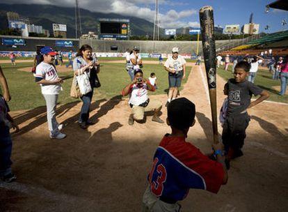 Niños en un estadio de béisbol en Caracas, imitando  las posturas de los grandes jugadores.