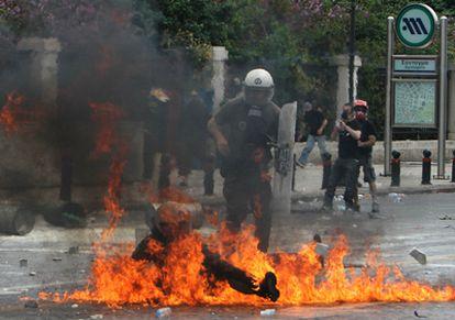 Un policía antidisturbios se revuelve en medio de las llamas de un cóctel molotov lanzado durante las protestas frente al Parlamento en Atenas.