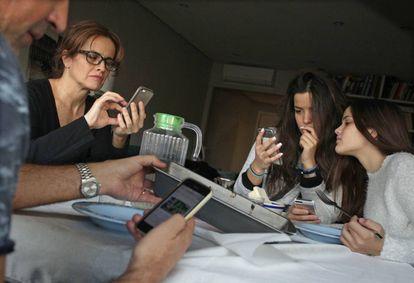 """Unos padres con sus hijas almorzando mientras """"chatean"""" y navegan con sus móviles."""