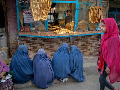 Cuatro mujeres con burka esperan pan gratis en una panadería de Kabul, el jueves.