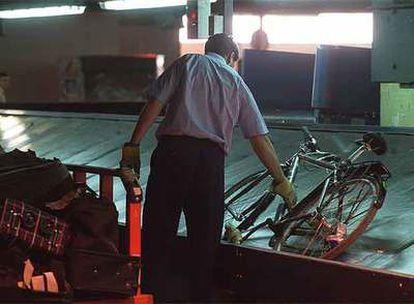 Un operario recoge equipaje en el aeropuerto de Barajas.