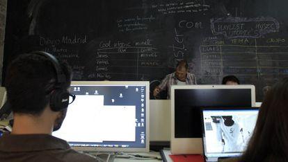 Estudiantes en un aula de 'coworking' con sus ordenadores.