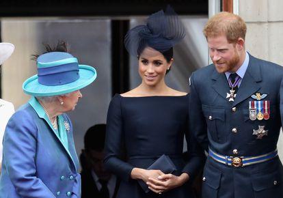 Enrique de Inglaterra y Meghan Markle, duques de Sussex, contemplan junto a la reina Isabel II un desfile aéreo desde el palacio de Buckingham, el 10 de julio de 2018.