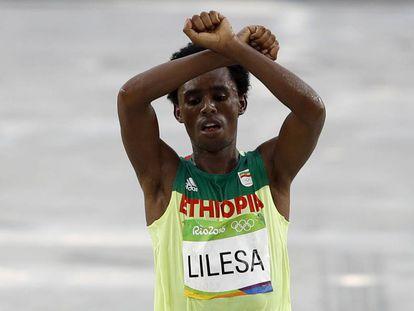 Feyisa Lilesa realiza su gesto crítico al llegar a la meta.