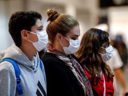 Viajeros con mascarillas en un aeropuerto de Brasil. En vídeo, las restricciones aplicadas en varios países de latinoamérica.
