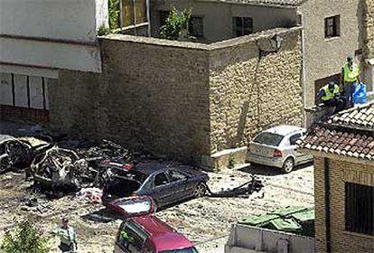 Los cadáveres aparecen en la foto cubiertos por una sábana entre los coches destrozados, mientras agentes de la Guardia Civil inspeccionan la zona.